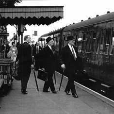 City commuters board their morning train at Hadham Station, led here by Mr Harry Sporborg of Hambro's Bank. c1958. | Photographer unknown; lent by Stephen Ruff