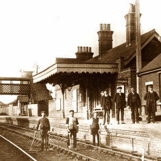 Hadham Station around 1913. The station master (frock coat) and station staff stand on the platform, while the permanent way men stay on their track. | Lent by Stephen Ruff