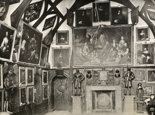 The banquetting hall c1910.  The caretaker is sitting on a chair to the right. | Hertfordshire Archives and Local Studies