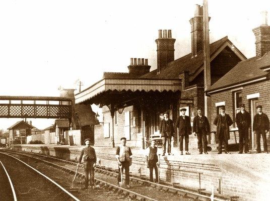 Hadham Station c1913. The station master (frock coat) and station staff stand on the platform, while the permanent way men stay on their track. | Lent by Stephen Ruff