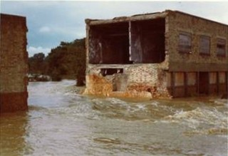 The floodwaters pasing through the remains of the mill | Anon.