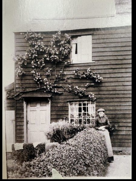 Oliver's mother about 1920 in house where Oliver was raised with his six siblings in Takeley in front of Piper's Windmill, run by Henry Piper assisted by his brother Peter. | Sheila Haley
