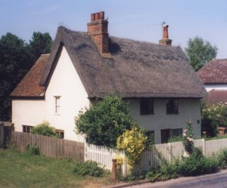 George Orwell's cottage as it is today with a thatched roof.  Orwell grew roses in his garden from Woolworth's seed packets. | Hertfordshire Archives and Local Studies (DEX1024/1/152/125)