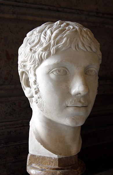A bust of Emperor Elagabalus. The bust is white and shows a young man with wavy hair.