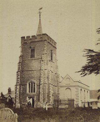 A photograph of Essendon church taken not long after Edward John Edwards was there. It is in sepia, and shows the church tower. A figure in old clothing is at the door of the church.   Hertfordshire Archives and Local Studies, DE/Gr/28/3/2.