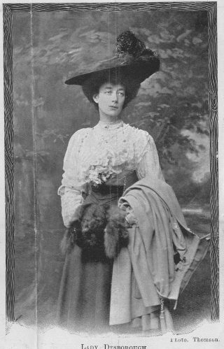 A black and white photograph of Ettie Desborough as a young lady. She wears a big hat and frilly white blouse and her hands are in a ladies muff.   Hertfordshire Archives and Local Studies, DE/Rv/F88.