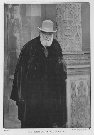 A photograph of Robert Gascoyne-Cecil, 3rd Marquess of Salisbury. It is in black and white and shows him at the entrance of Hatfield House.   Hertfordshire Archives and Local Studies DE/Gr/36.