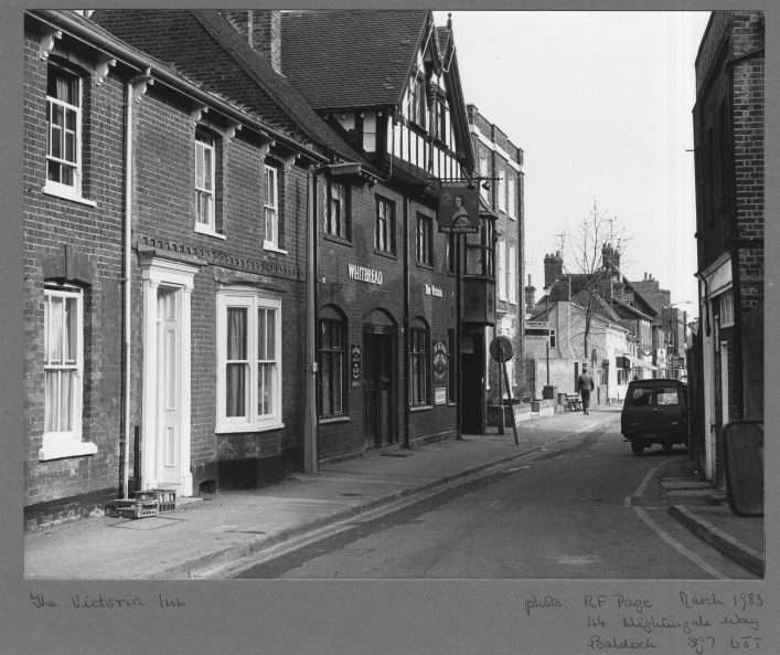 A black and white photograph of the Victoria pub in Baldock which used to be the Sun pub. The scene looks at the pub down the street, with a few other buildings visible. | Hertfordshire Archives and Local Studies, Local Studies Library image collection.