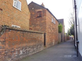 Roe's almshouse looking along Pepper Alley. The end wall of Wynne's almshouse is on the left. Nov 2017   Colin Wilson