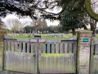 The gates of God's Acre cemetery with a Commonwealth War Graves small sign