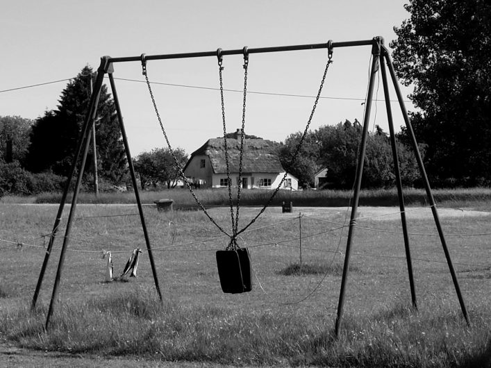 A swing which has been tied up so it cannot be used with Roe Green in the background | Toby Shelley