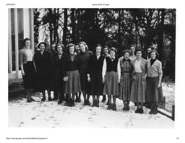 A group of ladies outside Scott House in Hertford with a window of the building on the left and evergreen trees in the background. A light covering of snow is on the ground but none of the ladies is wearing a coat and some are not wearing boots!   Julia Rizzi
