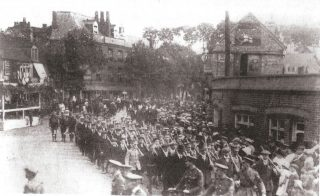 A group of soldiers has just wheeled right. They are followed by lines of men without uniforms but with rifles or makeshift rifles shouldered. There is a group of people mainly women and children watching in the bottom right hand corner. On the left middle is a saluting station. There is a single storey building with a pipe chimney on the right with a three-storey building behind. Further back on the side of the road are large trees in the middle with more multi-storey buildings on the left. | Hertfordshire Archives and Local Studies