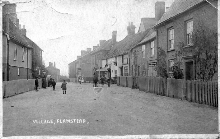 View down Trowley Hill Road with villagers, Bell pub and shop on the right, b&w photo from the 1900s | C Motley postcard collection