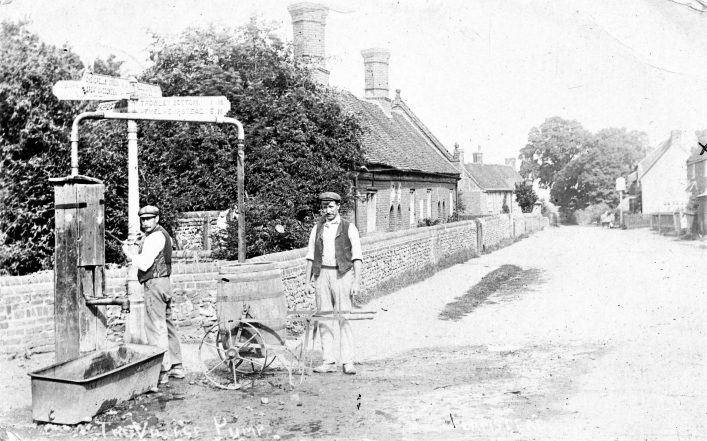 Men with a barrel at the village pump at the end of High Street in the 1900s, b&w photo | C Motley postcard collection