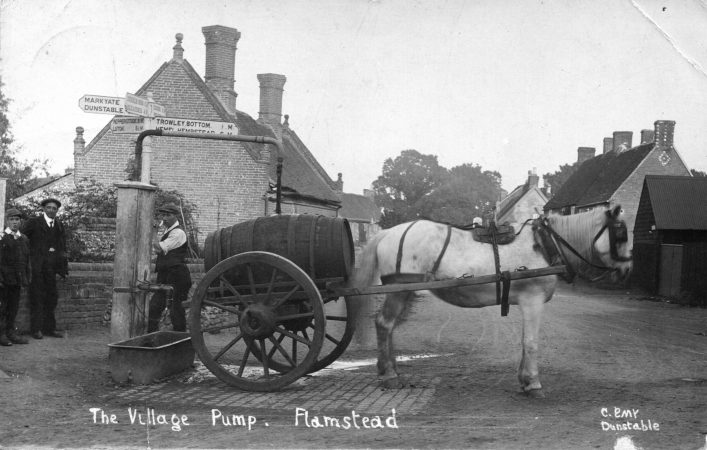 Horse and cart and villagers at the village pump, High Street, 1920s, b&w photo | C Emy; C Motley postcard collection