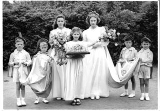 Mayday Queen with two princesses all wearing white dresses. The queen and the taller princess on her right are are holding bouquets with a smaller maid in front holding a bouquet on a cushion. Either side of the girls are two page boys dressed in shirts and shorts with white socks and shoes and each wearing a hat with a feather. The pages are holding the ends of the queen's robe.