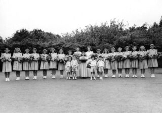 The two queens and the maid as in the previous photograph with the pages in line with the maid and eight maids of honour either side of the queens. The maids are all holding bouquets of flowers.