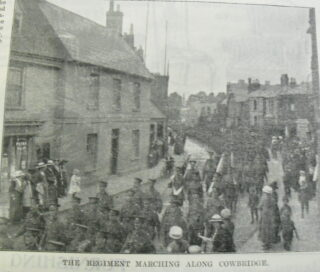 The Hertfordshire Regiment parading along Cowbridge with people cheering and houses at the side and in the background | Hertfordshire Mercury