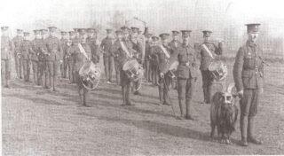A soldier leading a ram followed by drummers and buglers posed with sticks high and bugles at the men's sides | Hertfordshire Archives and Local Studies
