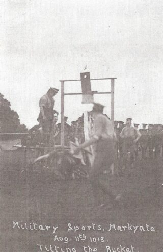 An indistinct image of soldiers in army shirts with sleeves rolled up and army trousers playing Tilting the Bucket' | Hertfordshire Archives and Local Studies