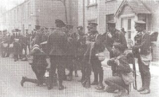 Soldiers loaded with their packs but off duty milling around in front of terraced houses. There is one street light behind the troops in the middle of the pscene | Hertfordshire Archives and Local Studies