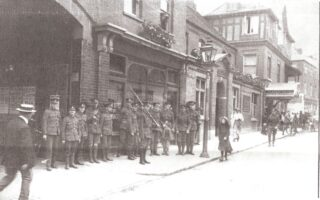 A dozen soldiers in uniform, one in shorts and one wearing a kilt in front of a public house with an open gate into a court yard. In front of the soldiers is another with his rifle and bayonet shouldered. A man in a suit wearing a boater is walking towards them from the left with a girl wearing a hat walking the other way in London Road,. There is a soldier probably an officer walking a few steps behind the girland a number of people in the distance milling around what is probably a cinema/theatre.. Above the ground floors is a window box and and at the end of the row of soldiers where the girl is walking is a lamp post.