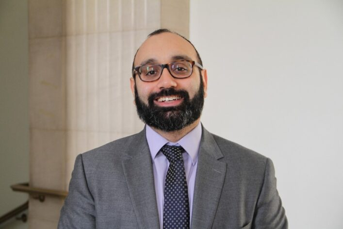 Photo of Faisal smiling and wearing a suit