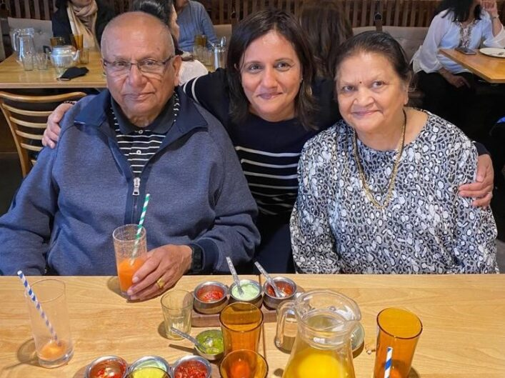 Family picture of rushma and her parents at a restaurant