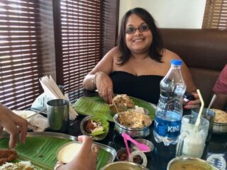 me in Indian eating  Biriyani and chutney with my fingers on a banana leaf