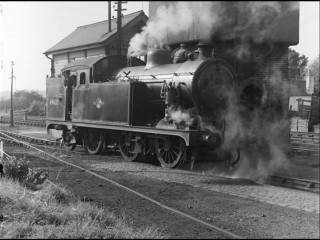 N7 tank locomotive taking on water from the tower behind the signal box at Buntingford Station, September 1958. | © Michael Covey-Crump