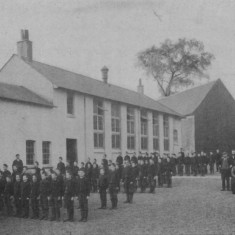 Boys and staff on parade outside the schoolhouse | These buildings were designed by the architect Philip Webb