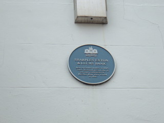 The plaque on the wall of Barclay's Bank, listing the former owners.