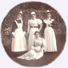 Group of smiling maids in a garden, c.1900: