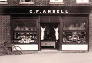 Outside of Ansell Butcher's shop, c. 1907. Blinds and canopies offered protection from rain and sunlight. Some Butchers opted to locate their shop on the shadier side of the street.
