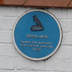 GREENLAWNS: This plaque on the wall of the 'Green Man' public house marks the area of the town's public bowling greens. At the rear of the Green Man is an area marked out for Petanque, the continental version played on a shingle piste, thus keeping up the tradition of the site. | Tim Shepherd