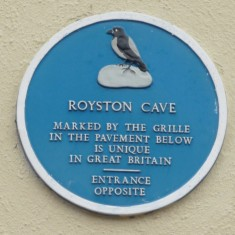 ROYSTON CAVE: Situated directly underneath this plaque. Despite the numerous carvings in the chalk bell chamber, the origin and purpose of the cave are still uncertain. The cave entrance is in the little courtyard opposite the plaque. | Tim Shepherd