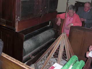 One of the barrels in the organ being shown to visitors by Ruth Swallow